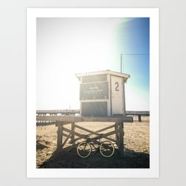 Bike leaning against lifeguard hut on beach Art Print