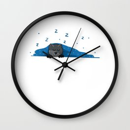 A Cute little gray kitten sleeps under a fur blue with dots blanket Wall Clock