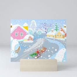 winter decorative landscape in naive style, winter village and santa claus on sleigh with christmas Mini Art Print