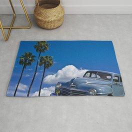Vintage Blue Plymouth Automobile against Palm Trees and Cloudy Blue Sky Rug