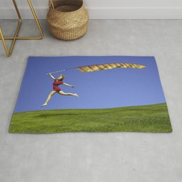 Freedom - A young girl jumping with a colorful kite banner on a clear blue sky day Rug