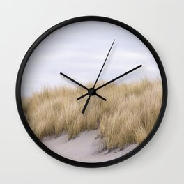 Field of grass growing in the sand Wall Clock