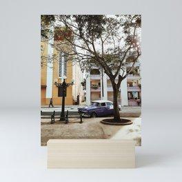 BLUE SEDAN PARKED NEAR WHITE BUILDING Mini Art Print