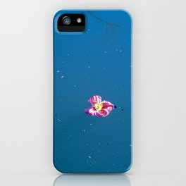 A pink blossom floating in a contrast blue lake iPhone Case