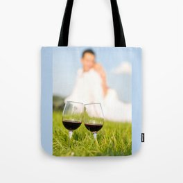 Two wineglasses with red wine in grass Tote Bag