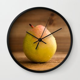 One fresh pear with water drops on rustic wood against a rustic wooden background close front view Wall Clock
