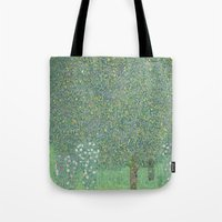 gustav klimt Tote Bags featuring Rosebushes under the Trees - Gustav Klimt by ArtMasters