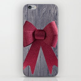 Big red Christmas shiny bow on a wooden background iPhone Skin