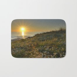 Sunset at the beach. White flowers on the sand Bath Mat