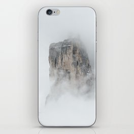Climbing a mountain in the clouds iPhone Skin