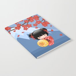 Japanese Red Sakura Kokeshi Doll on Blue Notebook