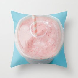 Top view of a strawberry smoothie in a plastic cup with a straw on a blue background. Throw Pillow