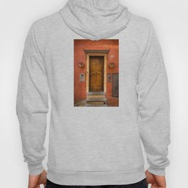 Wooden door of Tuscany with typical bright colors on its walls. Next to two small pots with flowers Hoody