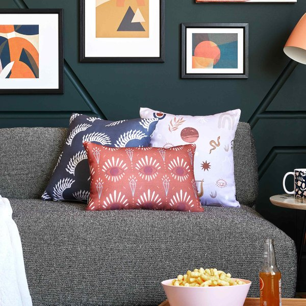 sofa with pillows, throw blanket and floral floor pillow