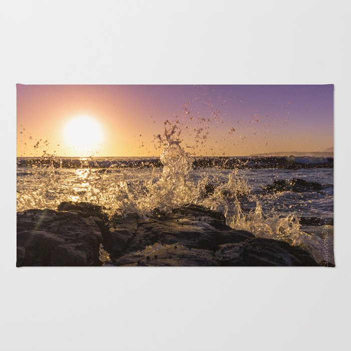 Magical sunset and waves breaking over rocky beach Rug