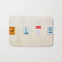 Signs on a corrugated metal wall Bath Mat