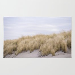 Field of grass growing in the sand Rug