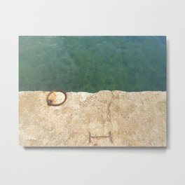 Teal waters and a rusty ring in a dock Metal Print