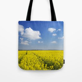 Path through blooming canola under a blue sky with clouds Tote Bag