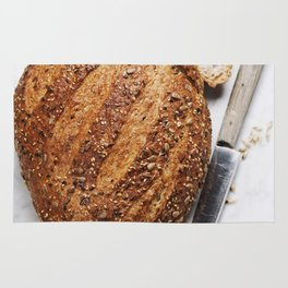 Large loaf of bread on white marble background Rug