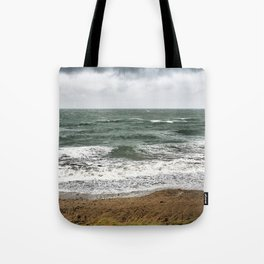 Land and sea under stormy clouds Tote Bag