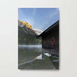 Boathouse with lifesaver Portrait. Amazing shot of a wooden house in the Ferchensee lake in Bavaria, Germany, in front of a mountain belonging to the Alps. Scenic foggy morning scenery at sunrise. Metal Print