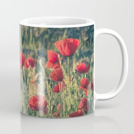Field covered with red flowers illuminated by the sunrise sun. Flowers of delicate petals in the mea Coffee Mug