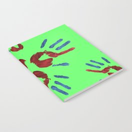 Red palm with blue fingers on neon green Notebook