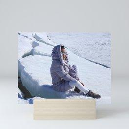 Girl in warm down-padded coat enjoys a look at snow top. Mini Art Print