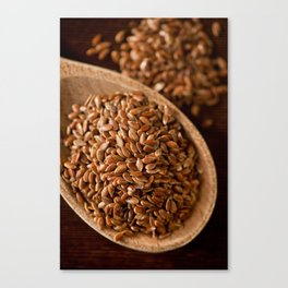 Brown flax seeds portion on wooden spoon Canvas Print