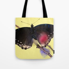 Tropical butterfly sitting on the colored bush over yellow background Tote Bag