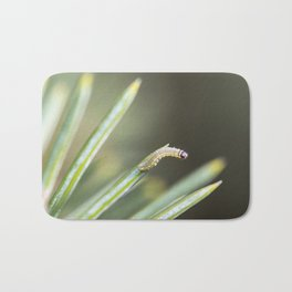 Tiny inchworm on a pine needle Bath Mat