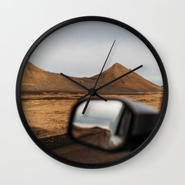 View of red mountains through a car window in north Iceland Wall Clock