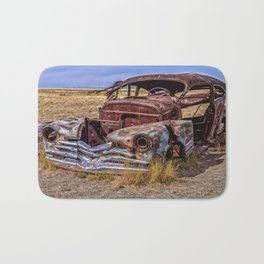 Abandoned car in Badlands ghost town Bath Mat