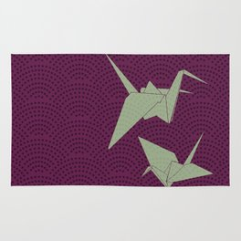 Origami paper cranes on purple waves Rug
