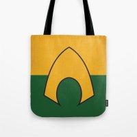 dc comics Tote Bags featuring Aquaman Logo Minimalist Art Print DC Comics by The Retro Inc
