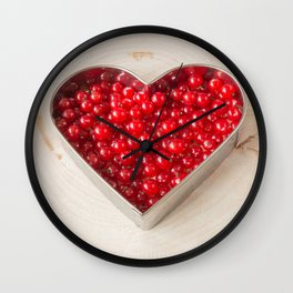 Currants in heart shaped cookie cutter on wood Wall Clock