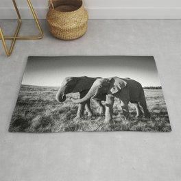 Elephant friends walk together along African savanna Rug