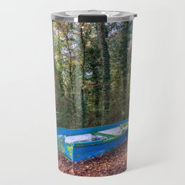 Old blue and green boat abandoned aground in a forest in a natural park Travel Mug