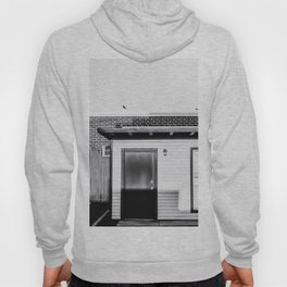 wood building with brick building background in black and white Hoody