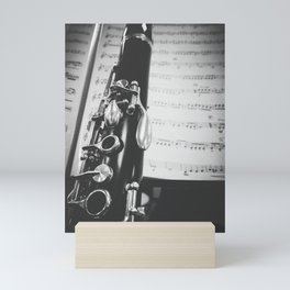 Part of a clarinet on musical score black and white Mini Art Print