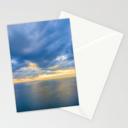 Aerial panoramic view of ocean water and beautiful blue skies at glowing yellow sunset. Nothing but water and clouds Stationery Cards