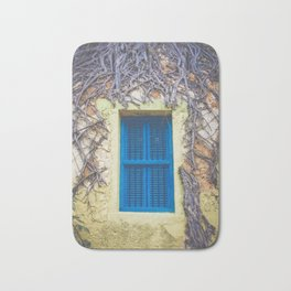 blue shutter window in yellow building with creeping vines Bath Mat