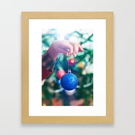 Children's hand with blue Christmas toy ball Framed Art Print
