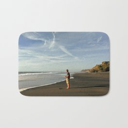 boy on black sand beach in new zealand Bath Mat