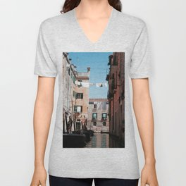 SEVERAL BOATS DOCKING ON BODY OF WATER NEAR MID RISE BUILDING Unisex V-Neck