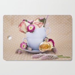 Roses and tea cups still life photo Cutting Board