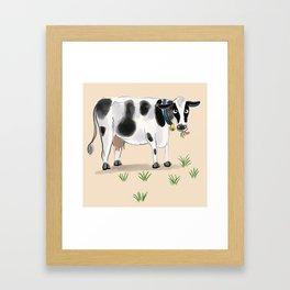 Cute cow eating grass Framed Art Print