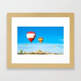 Colorful hot air balloons flying near Uchisar castle at sunrise, CappadociaTurkey Framed Art Print