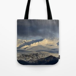 Snowy mountains through the clouds. Tote Bag